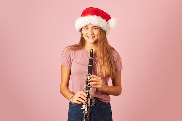 Молодая исполнительница женщина играет на кларнете и в шляпе санта-клауса