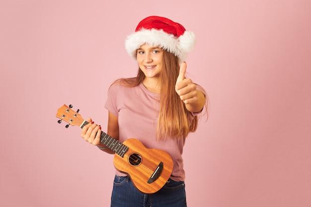 Молодая исполнительница играет на укулеле и носит шляпу санта-клауса с большим пальцем вверх на розовом