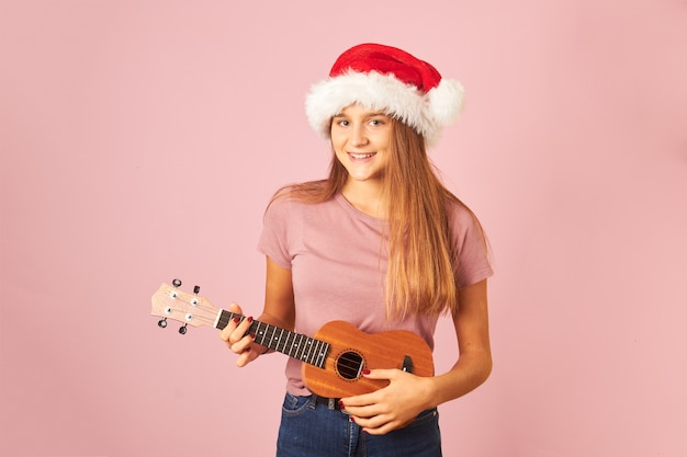 Young performer woman playing ukulele and wearing santa claus hat on a pink