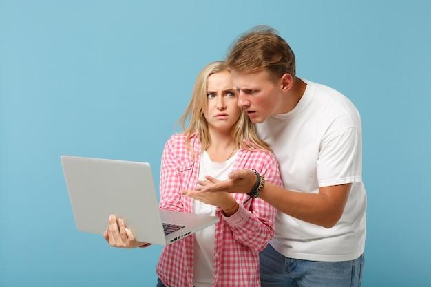 Молодая озадаченная пара друзей мужчина и женщина в белых розовых пустых пустых футболках позирует