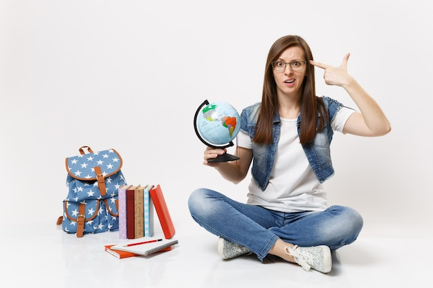 Young perplexed woman student holding globe putting hand to head like pistol for shoot sitting near backpack, school books isolated