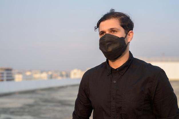 コロナウイルスの発生と汚染からの保護のためのマスクを着用しながら考えて若いペルシャ実業家