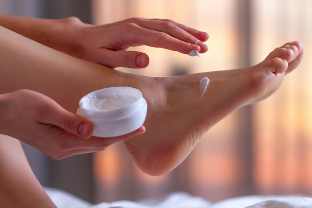 Young person caring about her feet and applying hydrating, moisturizing cream. foot and skin care.