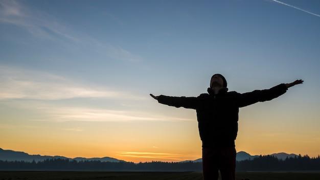 Молодой человек празднует восход или закат, стоя с вытянутыми руками на фоне красочного оранжевого неба.