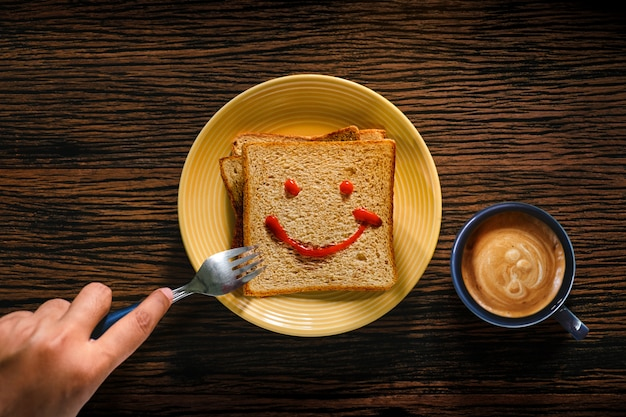 Young person eating bread and coffee cup in breakfast time