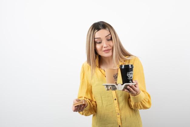 Giovane in possesso di tazze di caffè e guardando il coperchio.