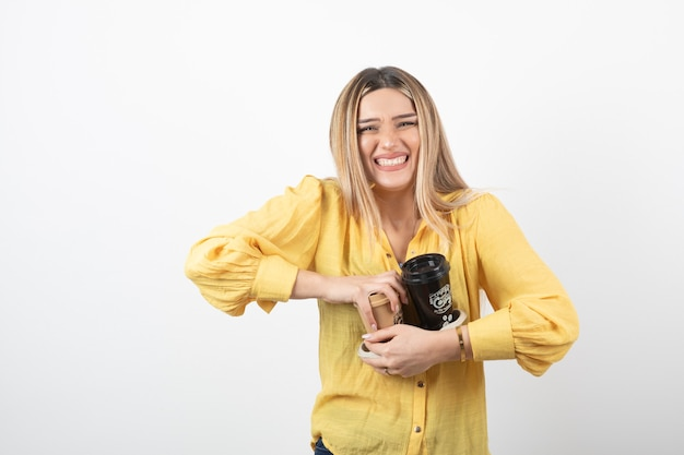 Young person holding cups of coffee on white wall.