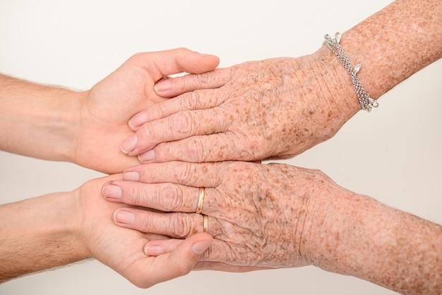 노인의 손을 잡고 젊은 사람을 닫습니다