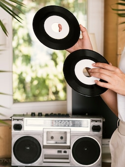 Young person holding vintage vinyl records indoors