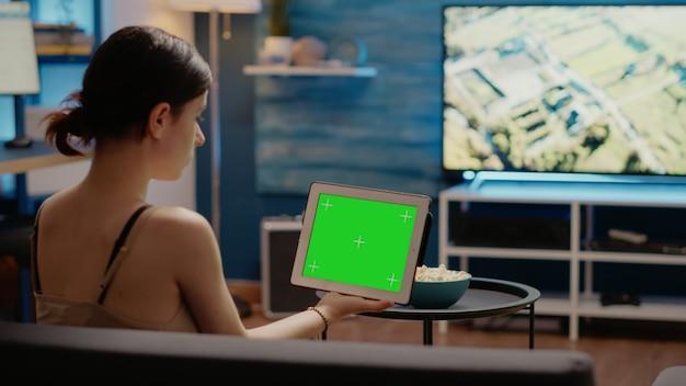 水平方向の緑色の画面でタブレットを見ている若い人