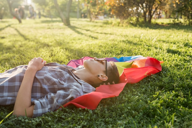 Young person lying on rainbow flag