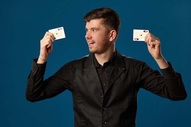 젊은 사람, 포커 초보자, 검은 조끼와 셔츠. 두 개의 카드 놀이를 들고 흥분을 찾고 있습니다. 블루 스튜디오 배경 포즈. 도박, 카지노. 확대.