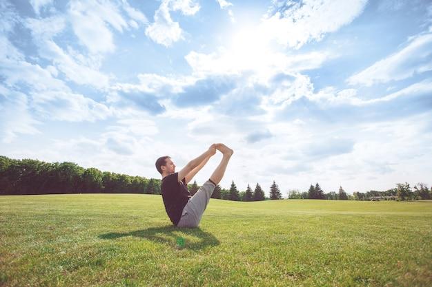Молодой человек занимается йогой на открытом воздухе здорового образа жизни