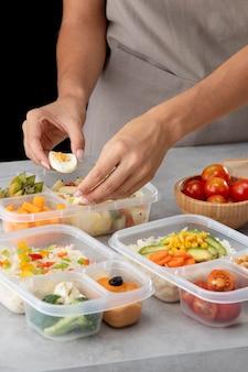 Giovane che pratica la cottura in batch con cibo sano