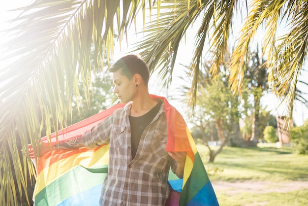 Young person standing with lgbt flag in park