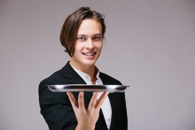 Young person in a suit holding an empty tray isolated on white wall