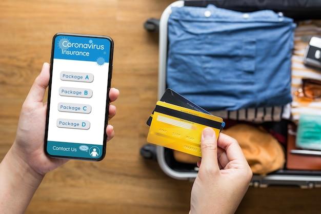 旅行に行く前に支払いコロナウイルス保険のためにスマートフォンでクレジットカードを使用している若者。健康と財務管理