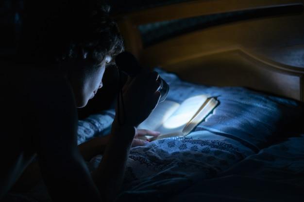 Молодой человек с легким фонариком читает книги в постели ночью в спальне