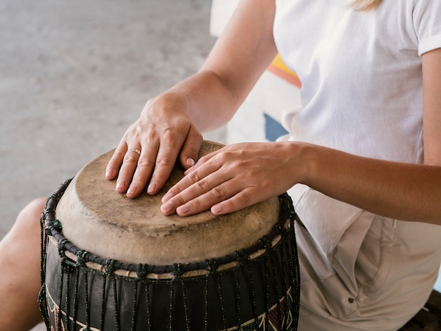 Young person with both hands on yuker drum
