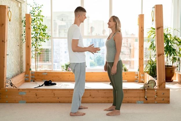 Молодой личный инструктор по йоге консультирует подходящую блондинку в спортивной одежде, стоящую перед ним и слушающую его рекомендации