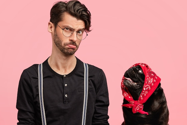 真面目な不機嫌そうな表情の若いペットの飼い主は、サスペンダー付きの黒いシャツを着て、犬と一緒に自由な時間を過ごし、ピンクの壁に向かってポーズをとります。人と動物の真の友情