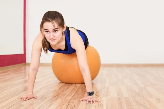 Young petite woman is training by doing push up with exercise ball in gym