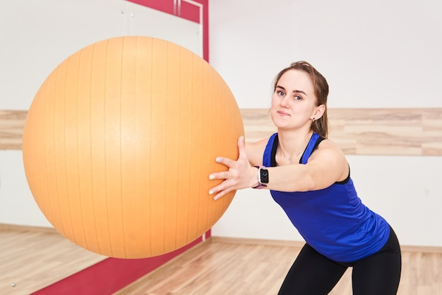 Young petite woman is training by doing squats with exercise ball in gym