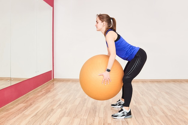 Young petite woman is training by doing squats with fyt ball in gym