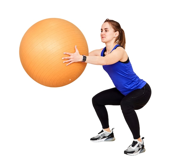 Young petite woman is training by doing squats with fyt ball, isolated on white background