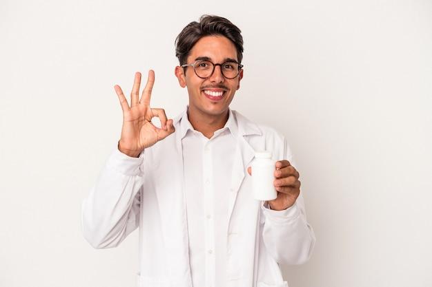 白い背景で隔離の丸薬を保持している若い薬剤師混血の男は陽気で自信を持って大丈夫なジェスチャーを示しています。