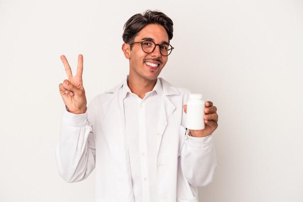 指で平和のシンボルを示す、楽しくてのんきな白い背景で隔離の丸薬を保持している若い薬剤師混血の男。