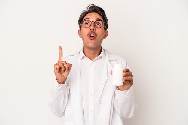 開いた口で逆さまを指している白い背景で隔離の丸薬を保持している若い薬剤師混血の男。