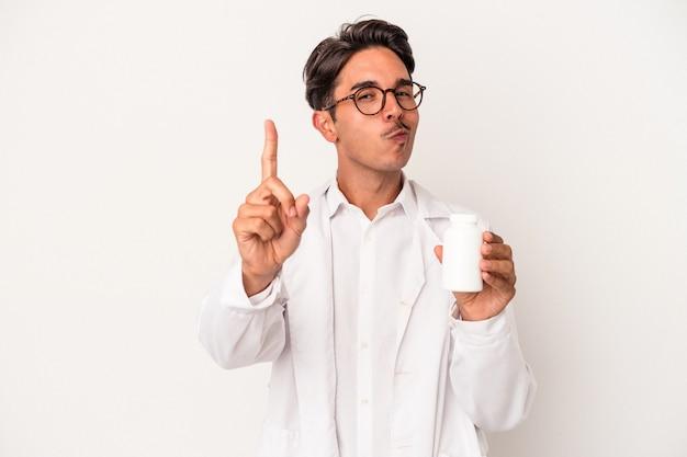 指でナンバーワンを示す白い背景で隔離の丸薬を保持している若い薬剤師混血の男。