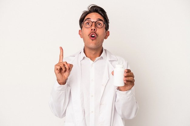 Young pharmacist mixed race man holding pills isolated on white background pointing upside with opened mouth.