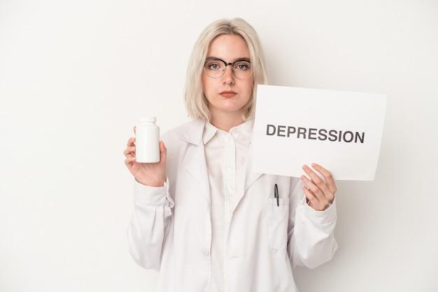 白い背景で隔離の丸薬とうつ病の段ボールを保持している若い薬剤師の女性
