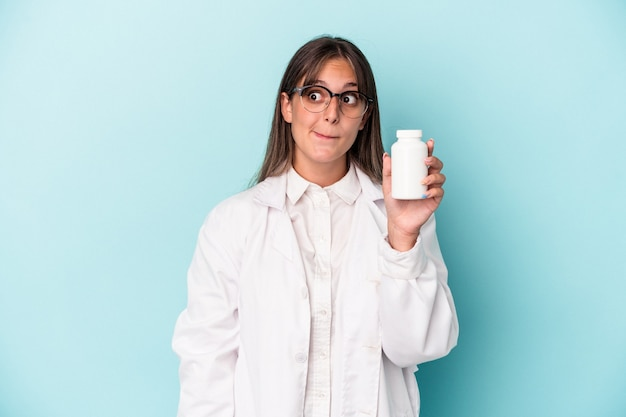 Young pharmacist woman holding pills isolated on blue background confused, feels doubtful and unsure.