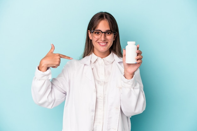 Young pharmacist woman holding pills isolated on blue background person pointing by hand to a shirt copy space, proud and confident