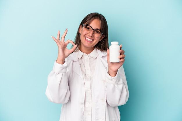 青の背景に分離された丸薬を保持している若い薬剤師の女性は、陽気で自信を持って大丈夫なジェスチャーを示しています。