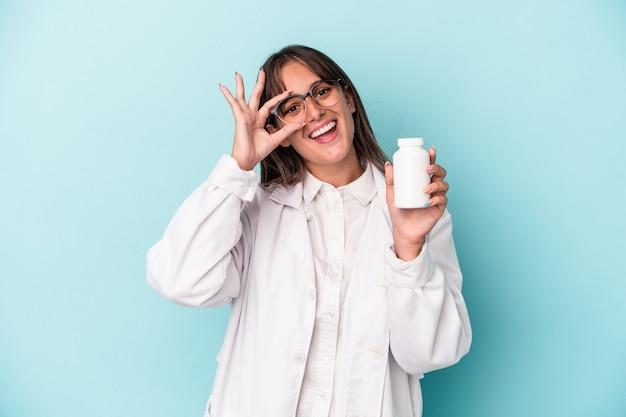 青い背景に分離された丸薬を保持している若い薬剤師の女性は、目に大丈夫なジェスチャーを維持して興奮しました。
