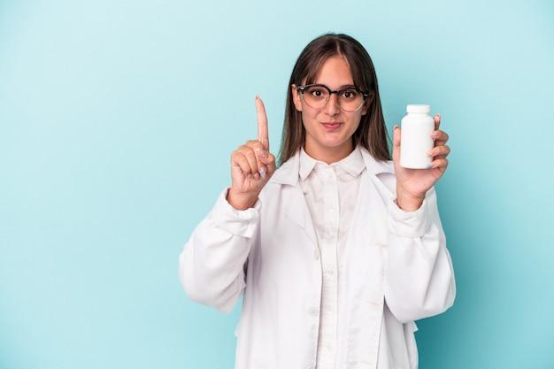 指でナンバーワンを示す青い背景で隔離の丸薬を保持している若い薬剤師の女性。
