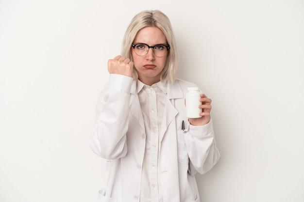 カメラに拳、積極的な表情を示す白い背景で隔離の丸薬を保持している若い薬剤師の女性。