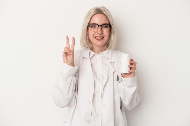 指で2番目を示す白い背景で隔離の丸薬を保持している若い薬剤師の女性。