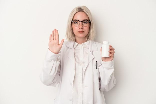 一時停止の標識を示す伸ばした手で立っている白い背景で隔離の丸薬を保持している若い薬剤師の女性は、あなたを防ぎます。