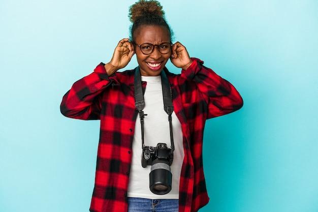 Афро-американских женщина молодой фотограф, изолированные на синем фоне, закрывая уши руками.