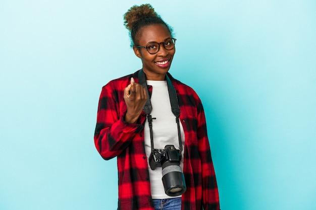 若い写真家アフリカ系アメリカ人の女性は、招待が近づくようにあなたに指で指している青い背景に分離されました。