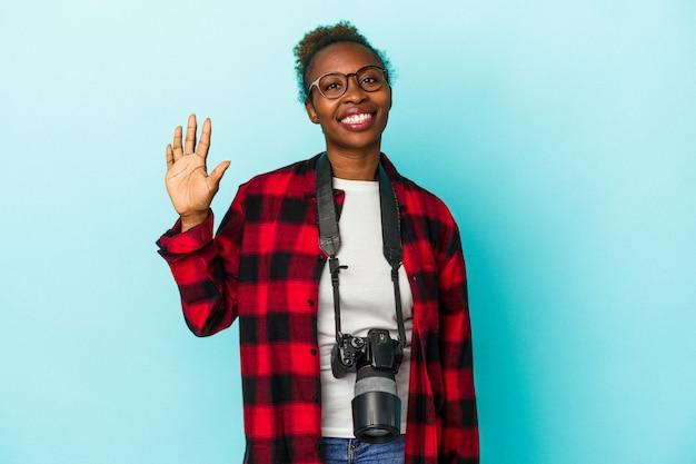 若い写真家アフリカ系アメリカ人の女性は、指で5番を示す陽気な笑顔の青い背景に分離されました。