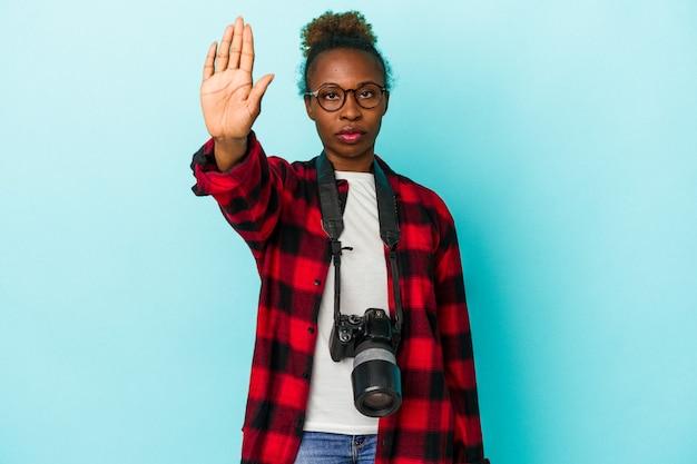 Афро-американских женщина молодой фотограф, изолированные на синем фоне, стоя с протянутой рукой, показывая знак остановки, предотвращая вас.