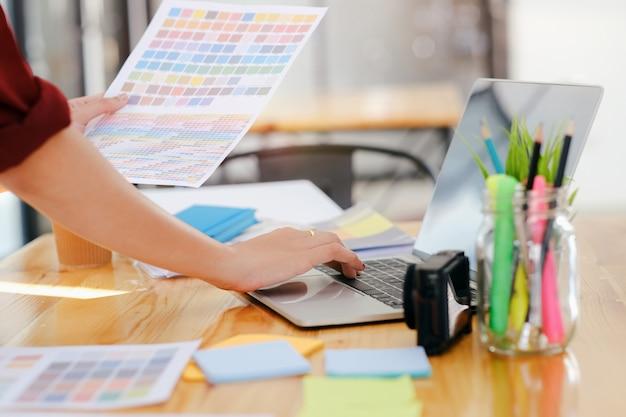 オフィスで働く若い写真家とグラフィックデザイナー。