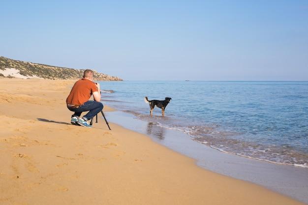 젊은 사진작가이자 비디오그래퍼는 삼각대에 카메라를 들고 바다와 강아지의 사진과 비디오를 만듭니다. 지중해.