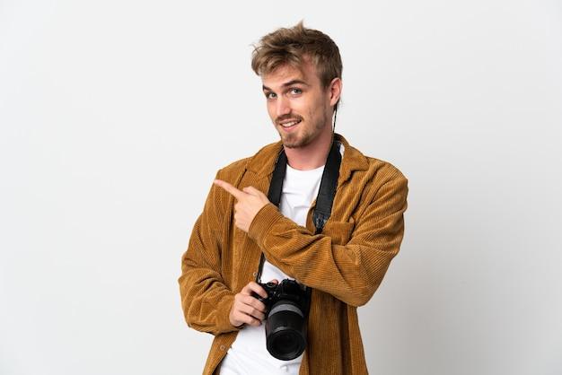 Молодой фотограф блондинка изолированы, указывая в сторону, чтобы представить продукт